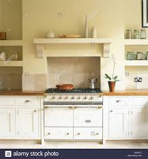 white range oven below shelf in country kitchen with white painted
