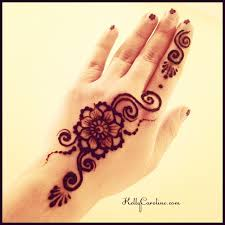 cute flower henna tattoo for the top of the hand with swirls