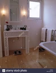 mirrored cabinet above trellis frame vanity unit in modern white