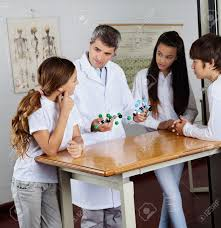 Student At Desk by Mature Male Teacher Explaining Molecular Structures To Students