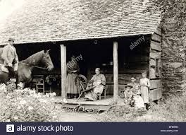 old woman at spinning wheel on log cabin porch stock photo