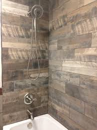 very rustic shower with the wood looking porcelain tiles on the