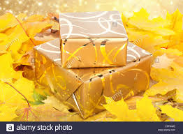 gold wrapping paper gift box in gold wrapping paper with autumn leaves on the abstract