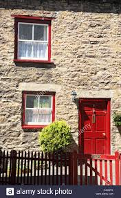 a traditional stone cottage with bright red painted door and