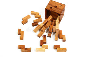 brown wooden cube puzzle with wooden pieces scattered around on