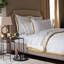 elegant bedroom gold chinoiserie screen white bedding brown trim