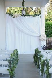 wedding backdrop garland draped ceremony backdrop with green garland and flower accents