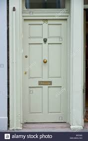 gray painted wooden paneled front door no 98 with brass letterbox