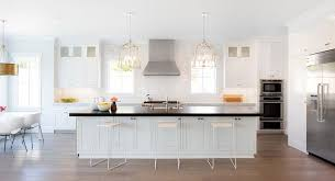 white kitchen island with black granite top white marble top island with gray spindle counter stools