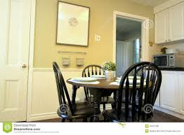 kitchen with white cabinets and round table and chairs stock photo