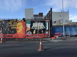 these murals lie at the center of a debate over northern ireland s the falls international peace wall a big tourist draw where large works of art