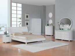 minimalist bedroom with white furniture including wardrobe and bed
