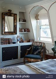 antique chair in front of arched dormer window in bedroom with