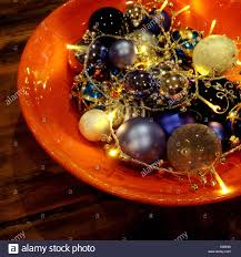 Christmas Decorations Lights In A Bowl by Orange Bowl On Wooden Table With Christmas Decorations And Lights