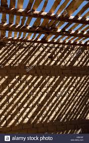 shadow stripes timber ceiling beams and slats on brick wall