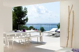 amazing white dining table furnished with benches of balcony