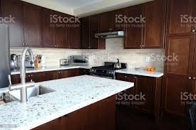 what color countertops go with brown cabinets domestic kitchen with quartz countertops and brown cabinetry stock photo image now