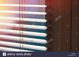 sunlight coming through venetian blinds by the window stock photo