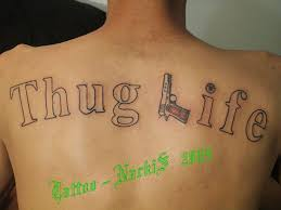 thug life lettering with gun tattoo on upper back life tattoos