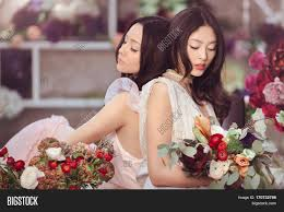 beautiful asian florist girls making bouquet of flowers on table