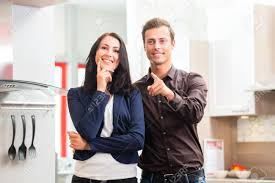 man and woman buying domestic kitchen in studio or furniture