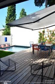 petite piscine enterree piscine en arrière plan entourée de gazon terrasse en bois au