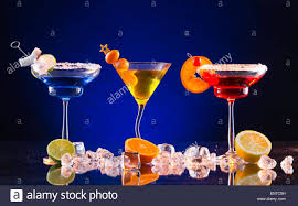 martini drinks martini drinks served on glass table with colored dark background