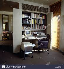 computer on desk below shelving in modern gray foldaway homeoffice