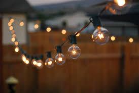 Stringing Lights In Backyard by A Traveling Wife Backyard Decor Globe String Lights