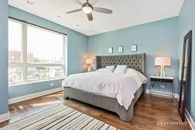 contemporary master bedroom with hardwood floors ceiling fan in