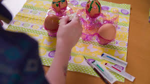 Decorating Easter Eggs Video by Squeezing Color Tube For Drawing On Egg 4k Over Shoulder View Of