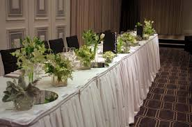 Bridal table decorations of white flowers in assorted vases