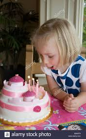 uk 4 year old blowing out candles on birthday cake stock