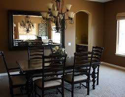 dining room with black walls and sunburst mirror wall decor