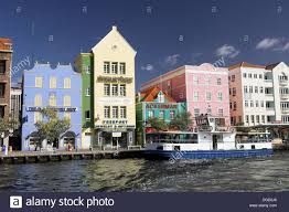 brightly colored buildings with dutch colonial architecture line