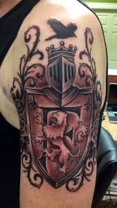 chest and half sleeve tattoos black and grey roaring lion in family crest tattoo on man left