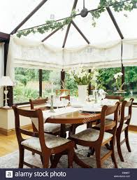 antique table and chairs in conservatory dining room with cream