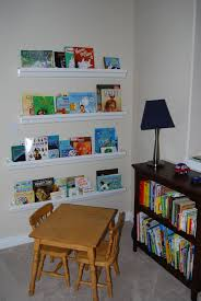 floating white wooden books shelves on the cream wall combined