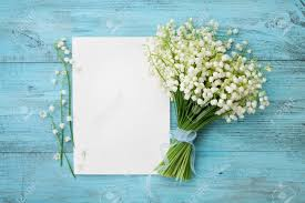 turquoise flowers bouquet of flowers of the valley and empty paper sheet on
