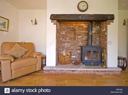 brick fireplace with wood burning stove and leather armchair stock