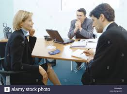 professional couple sitting in meeting with sales executive stock