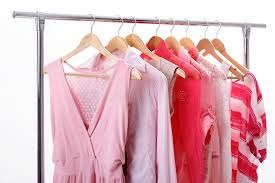 pink womens clothes on hangers on rack on white background clos