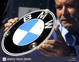 logo bmw dpa a man holds the bmw logo in his hands at the olympiahalle