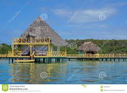 over water bungalow with thatch roof caribbean sea stock photo