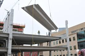 parking structure options precast vs cast in place schaefer a precast parking structure panel is being hoisted in by a crane with the assistance of