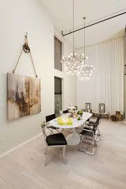 dining room with high ceiling and hanging contemporary chandeliers