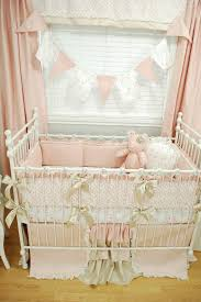 pink floral crib bedding with lace ruffles and golden bows for a