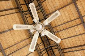 large ceiling fan under a thatched roof stock photo picture and