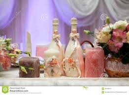 decorated champagne bottles candles and flowers on wedding table