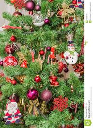 detail of green christmas tree with colored ornaments globes